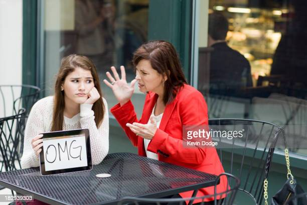 Caucasian girl with tablet as mother chastises her at cafe
