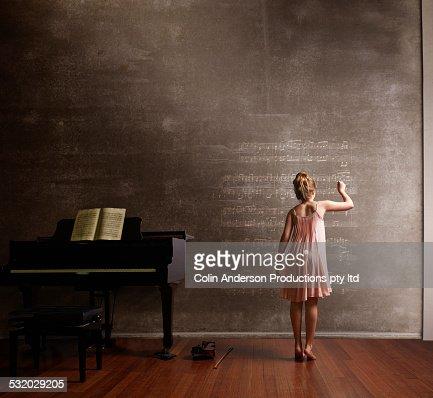 Caucasian girl writing music on blackboard