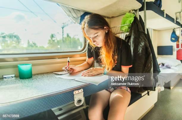 Caucasian girl writing on train