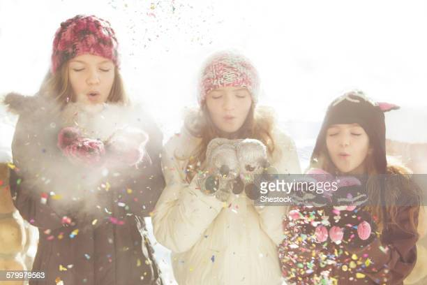 Caucasian girls blowing snow off mittens