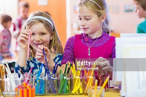 Caucasian girls choosing multicolor pencils in classroom