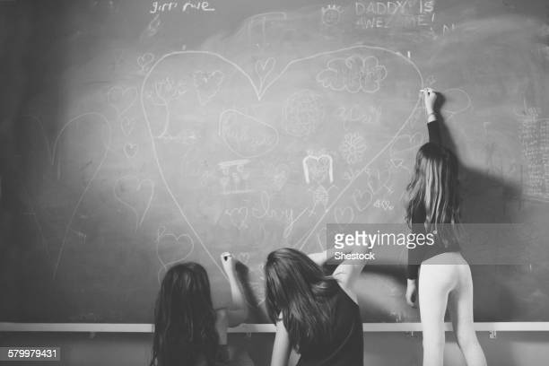 Caucasian girls drawing on classroom chalkboard
