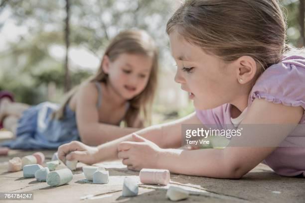 Caucasian girls drawing on sidewalk with chalk