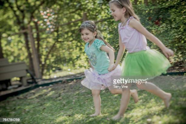 Caucasian girls holding hands and running in grass
