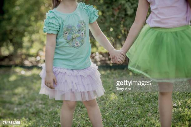 Caucasian girls holding hands in the grass