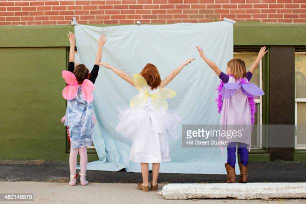 Caucasian girls in fairy costumes pretending to fly