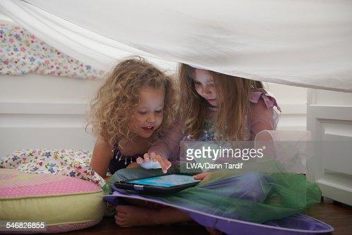 Caucasian girls in princess costume using digital tablet in blanket fort
