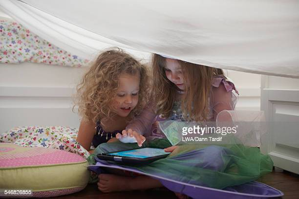 Caucasian girls in princess costume using digital tablet in blanket fort