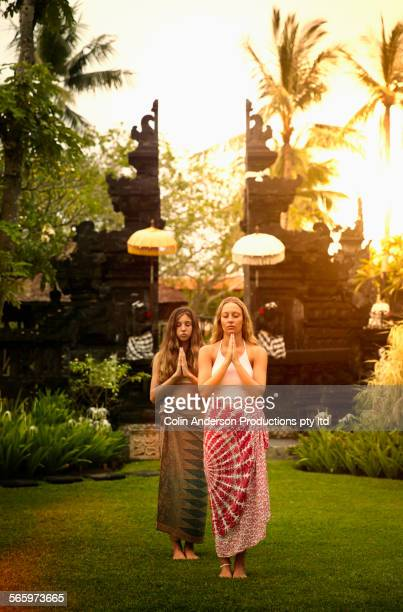 Caucasian girls meditating in garden