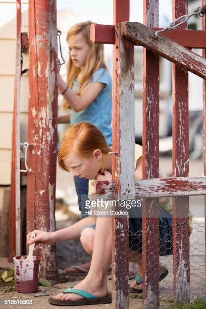 Caucasian girls painting fence