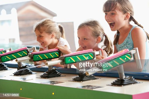 Caucasian girls playing at amusement park arcade
