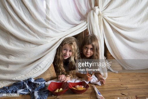 Caucasian girls playing in blanket fort
