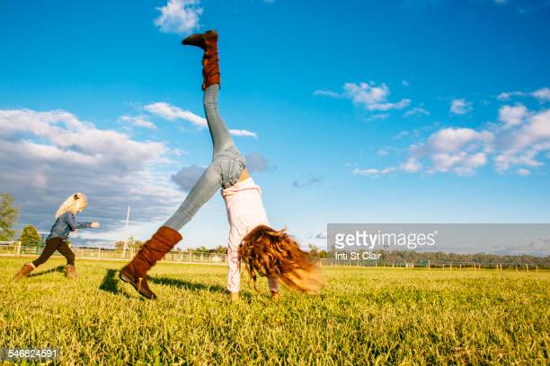 Caucasian girls playing in rural field