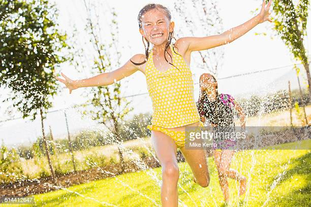 Caucasian girls playing in sprinkler in backyard