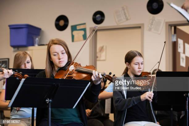 Caucasian girls playing violin in music class