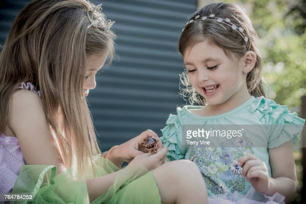 Caucasian girls playing with enormous ring