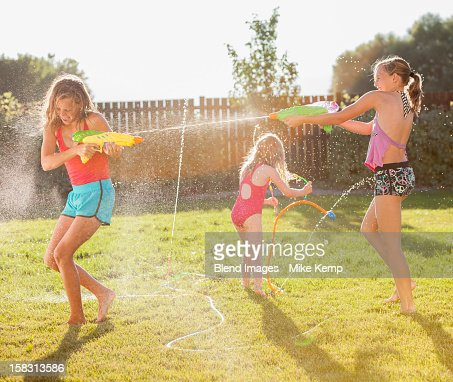 Caucasian girls shooting water guns
