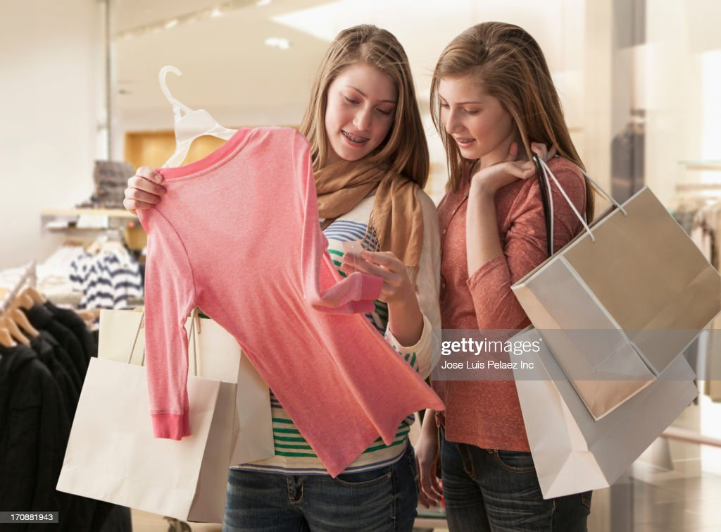 Caucasian girls shopping in clothes store : Stock Photo