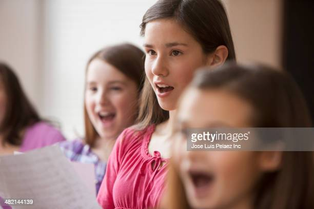 Caucasian girls singing in music class