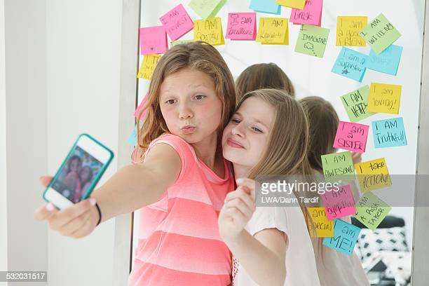 Caucasian girls taking cell phone selfie near adhesive note mirror