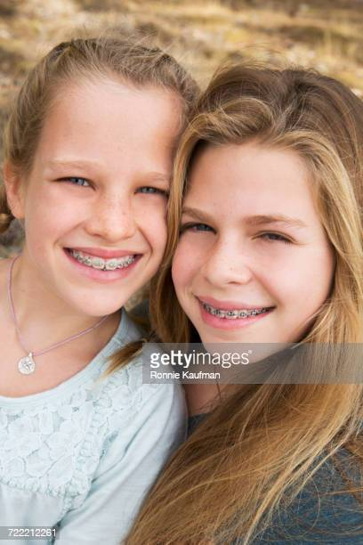 Caucasian girls with braces smiling cheek to cheek