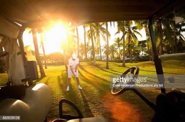 Caucasian golfer preparing on golf course viewed from golf cart