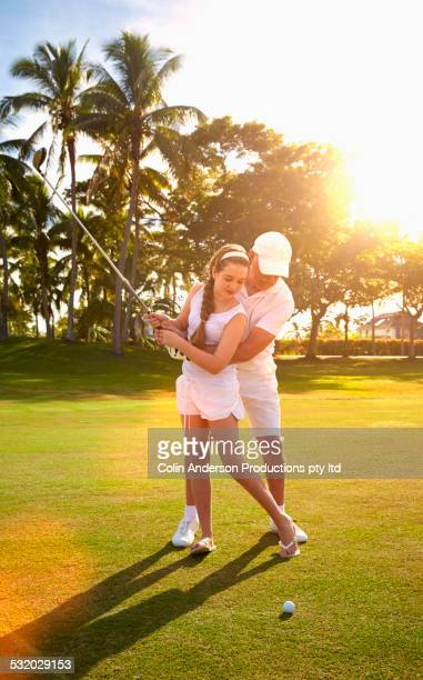 Caucasian golfer teaching granddaughter to play golf