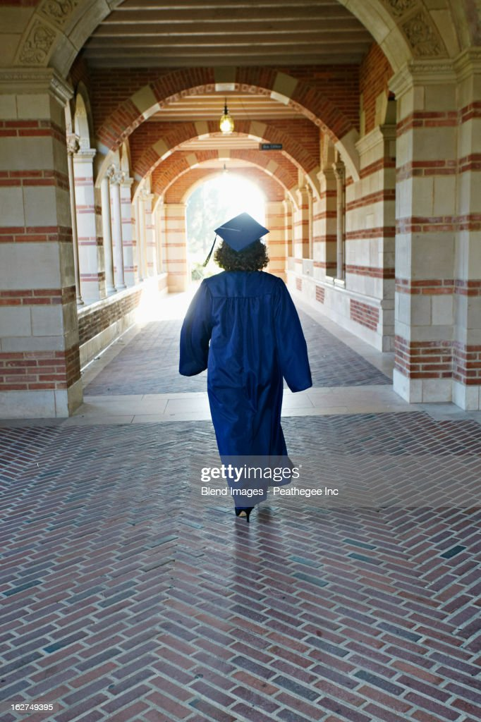 Caucasian graduate walking in portico : Stock Photo