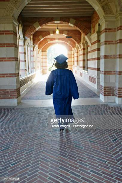 Caucasian graduate walking in portico