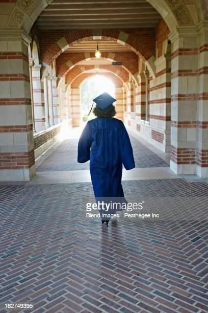 Caucasian graduate walking in portico