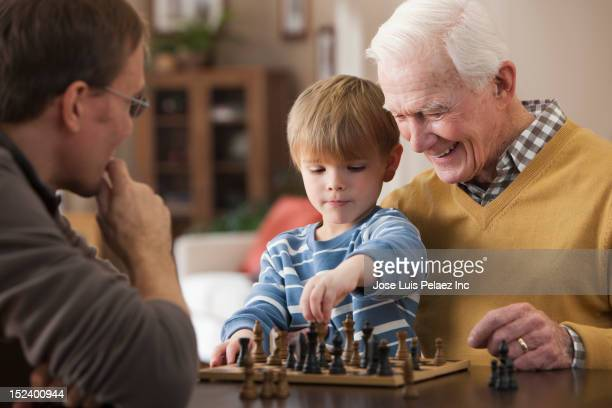 Caucasian grandfather and grandson playing chess