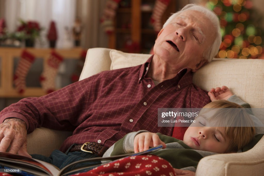Caucasian grandfather and grandson sleeping in chair