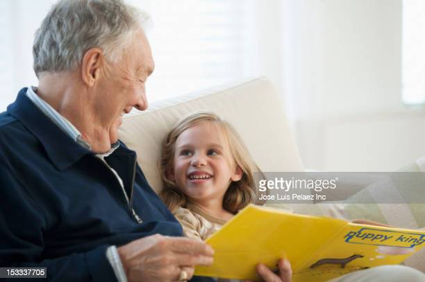 Caucasian grandfather reading book to granddaughter