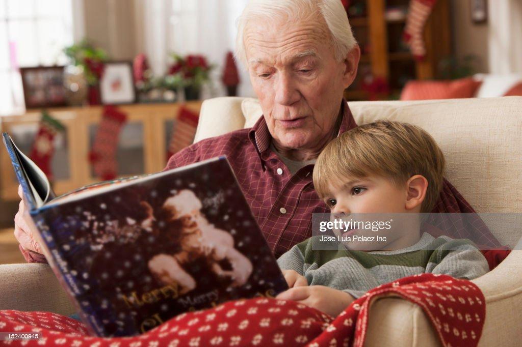 Caucasian grandfather reading book to grandson