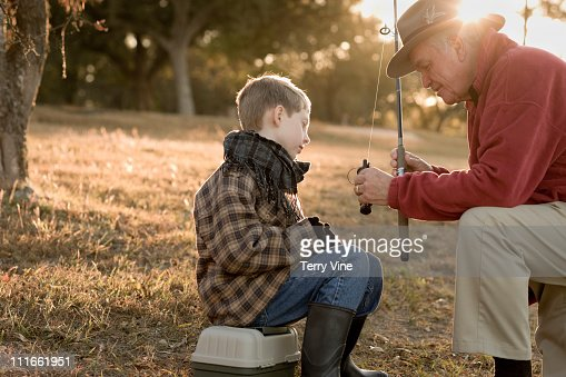 Caucasian grandfather teaching grandson to fish : Stock Photo