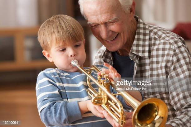 Caucasian grandfather watching grandson playing trumpet