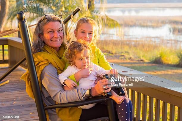 Caucasian grandmother and grandchildren using binoculars on porch