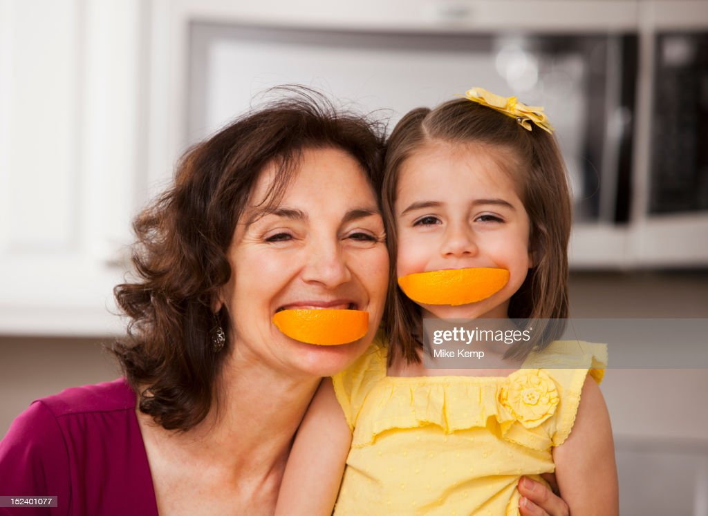 Caucasian grandmother and granddaughter eating fruit : Stock Photo