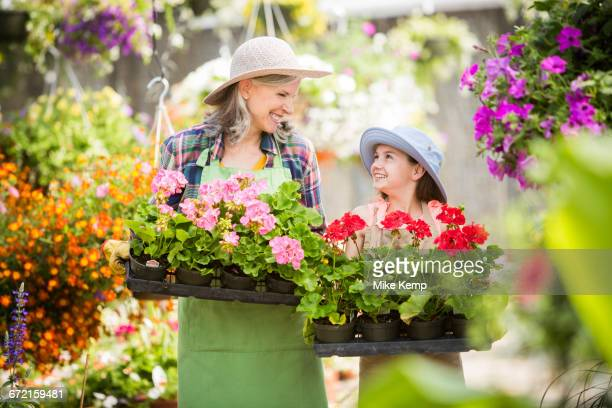 Caucasian grandmother and granddaughter holding potted plants in greenhouse