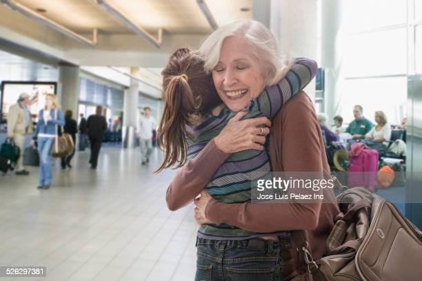 Caucasian grandmother and granddaughter hugging in airport