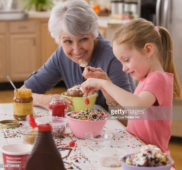 Caucasian grandmother and granddaughter making ice cream sundaes together