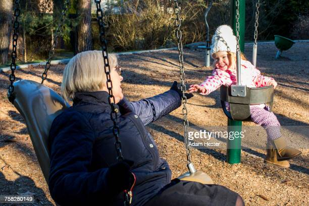 Caucasian grandmother and granddaughter on swings