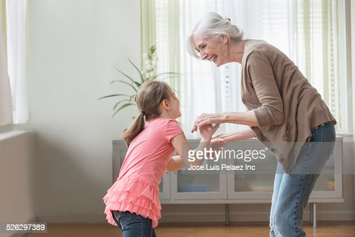 Caucasian grandmother and granddaughter playing in living room