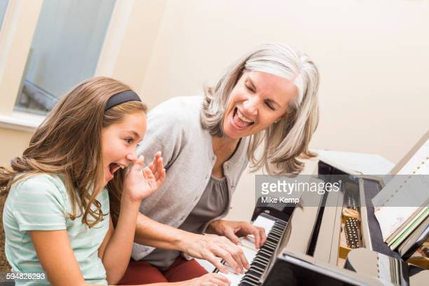 Caucasian grandmother and granddaughter playing piano