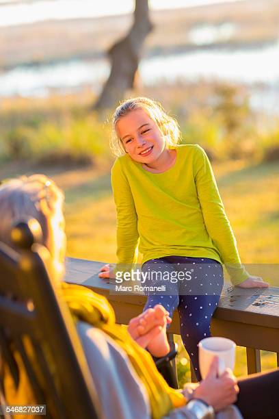 Caucasian grandmother and granddaughter relaxing on porch