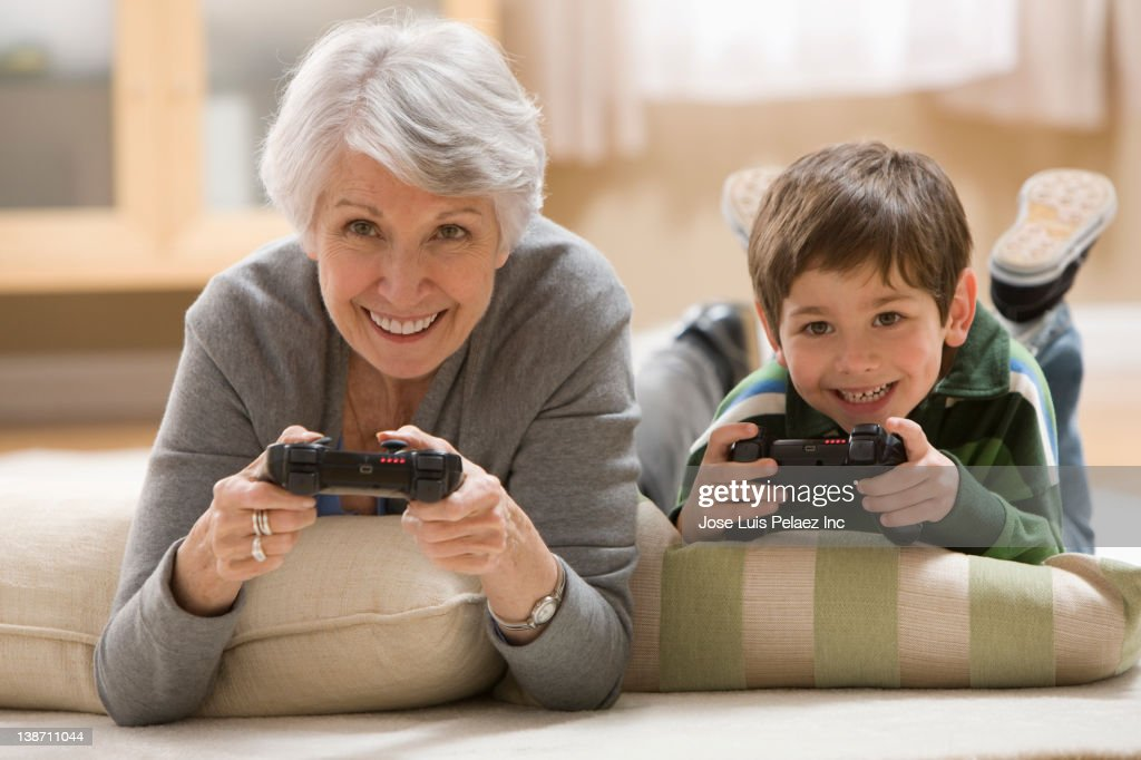 Caucasian grandmother and grandson playing video game