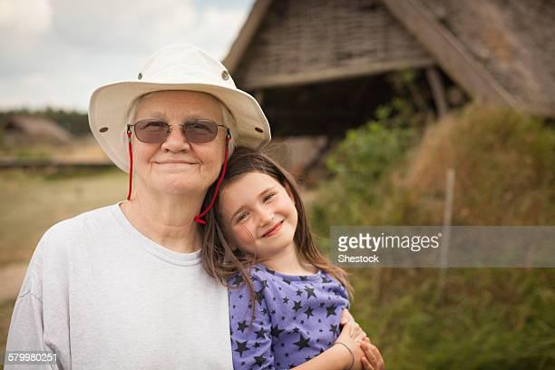 Caucasian grandmother hugging granddaughter in backyard