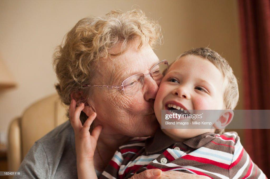 Caucasian grandmother kissing grandson : Stock Photo