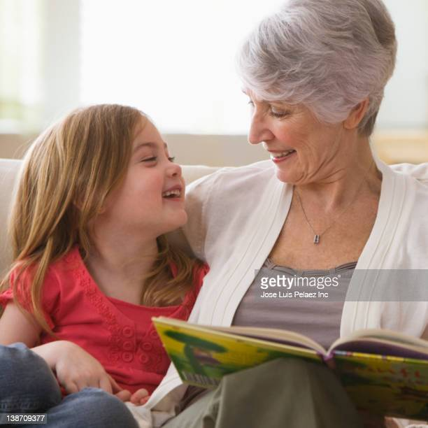 Caucasian grandmother reading book to granddaughter