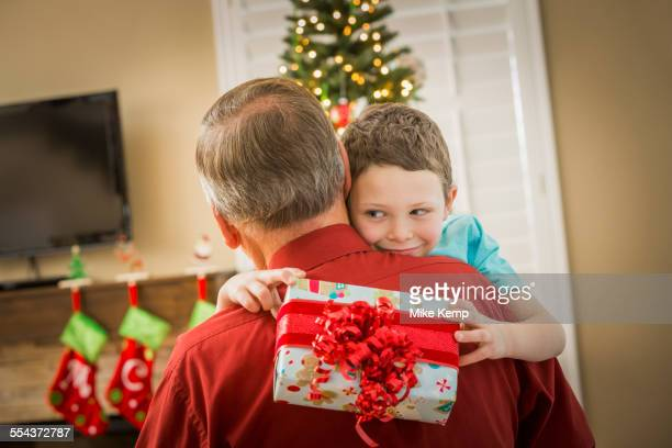 Caucasian grandson hugging grandfather with Christmas gift